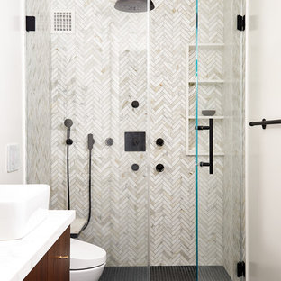 Kleines Modernes Duschbad mit flächenbündigen Schrankfronten, hellbraunen Holzschränken, Duschnische, Marmorfliesen, weißer Wandfarbe, Mosaik-Bodenfliesen, Aufsatzwaschbecken, schwarzem Boden, Falttür-Duschabtrennung und weißer Waschtischplatte in New York