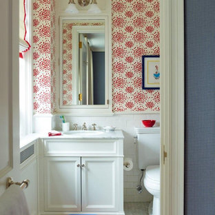 Photo of a small traditional kids bathroom in New York with an undermount sink, white cabinets, marble benchtops, a shower/bathtub combo, a two-piece toilet, multi-coloured walls, marble floors, recessed-panel cabinets and white tile.