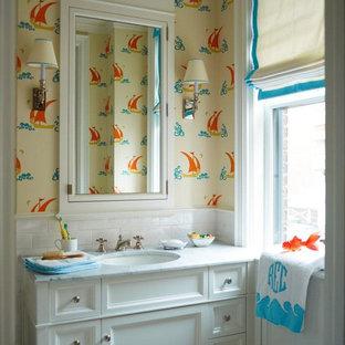 Immagine di una piccola stanza da bagno per bambini chic con lavabo sottopiano, ante lisce, ante bianche, top in marmo, vasca/doccia, WC a due pezzi, piastrelle grigie, pareti multicolore e pavimento in marmo