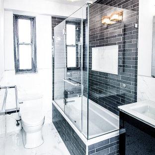 На фото: ванная комната среднего размера в стиле неоклассика (современная классика) с плоскими фасадами, черными фасадами, ванной в нише, душем над ванной, унитазом-моноблоком, черной плиткой, плиткой из сланца, белыми стенами, мраморным полом, душевой кабиной, монолитной раковиной, белым полом и душем с распашными дверями с