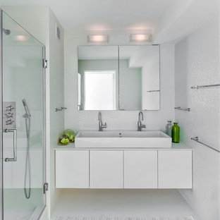 Inspiration for a contemporary master white tile alcove shower remodel in New York with white walls, a trough sink, flat-panel cabinets and white cabinets