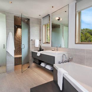 Foto di una stanza da bagno padronale minimal con lavabo a bacinella, ante lisce, ante grigie, vasca ad angolo, doccia a filo pavimento, piastrelle grigie e pareti bianche