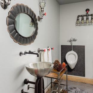Modelo de cuarto de baño urbano con urinario, paredes grises, suelo de cemento, lavabo sobreencimera y suelo gris