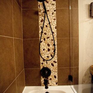 Imagen de cuarto de baño con ducha, rural, de tamaño medio, con armarios estilo shaker, puertas de armario naranjas, bañera encastrada, combinación de ducha y bañera, sanitario de una pieza, baldosas y/o azulejos marrones, baldosas y/o azulejos de cerámica, paredes beige, suelo de baldosas de porcelana, lavabo encastrado y encimera de granito