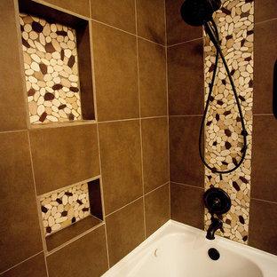 Foto de cuarto de baño con ducha, rural, de tamaño medio, con armarios estilo shaker, puertas de armario naranjas, bañera encastrada, combinación de ducha y bañera, sanitario de una pieza, baldosas y/o azulejos marrones, baldosas y/o azulejos de cerámica, paredes beige, suelo de baldosas de porcelana, lavabo encastrado y encimera de granito