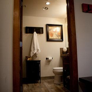 Foto de cuarto de baño con ducha, rústico, de tamaño medio, con armarios estilo shaker, puertas de armario naranjas, bañera encastrada, combinación de ducha y bañera, sanitario de una pieza, baldosas y/o azulejos marrones, baldosas y/o azulejos de cerámica, paredes beige, suelo de baldosas de porcelana, lavabo encastrado y encimera de granito