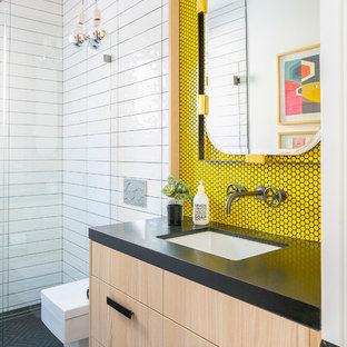 Salle de bain avec des portes de placard en bois clair et un ...