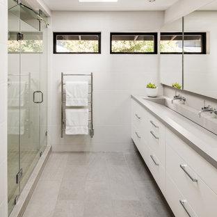 Modelo de cuarto de baño infantil, moderno, de tamaño medio, con armarios con paneles lisos, puertas de armario blancas, ducha abierta, sanitario de una pieza, baldosas y/o azulejos blancos, baldosas y/o azulejos de porcelana, paredes blancas, suelo de travertino, lavabo integrado, encimera de cuarzo compacto, suelo gris, ducha con puerta con bisagras y encimeras grises