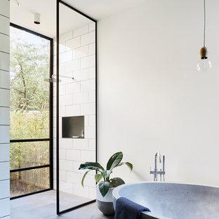 Ispirazione per una stanza da bagno padronale industriale con vasca freestanding, doccia a filo pavimento, piastrelle bianche, pareti bianche e doccia aperta