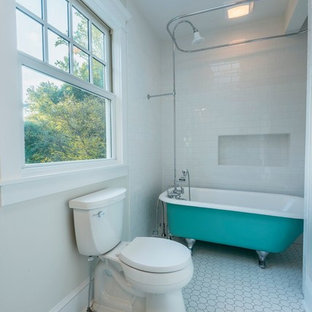 This is an example of a medium sized farmhouse family bathroom in Other with a claw-foot bath, a shower/bath combination, white walls, a shower curtain, a two-piece toilet, white tiles, metro tiles, mosaic tile flooring, a pedestal sink and white floors.