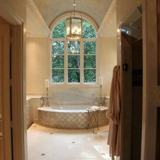 Exempel på ett stort medelhavsstil beige beige en-suite badrum, med ett undermonterat badkar, beige väggar, marmorgolv, vitt golv, luckor med infälld panel, beige skåp och marmorbänkskiva