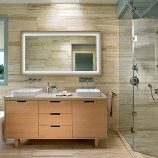 На фото: главная ванная комната среднего размера в скандинавском стиле с настольной раковиной, плоскими фасадами, светлыми деревянными фасадами, столешницей из известняка, отдельно стоящей ванной, двойным душем, инсталляцией, разноцветной плиткой, каменной плиткой и полом из известняка с