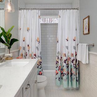 На фото: ванные комнаты в стиле современная классика с фасадами с утопленной филенкой, ванной в нише, душем над ванной, белой плиткой, плиткой кабанчик, серыми стенами, полом из мозаичной плитки и врезной раковиной