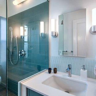 Ispirazione per una stanza da bagno padronale moderna di medie dimensioni con ante lisce, ante turchesi, doccia a filo pavimento, WC monopezzo, piastrelle blu, piastrelle di vetro, pareti bianche, pavimento in gres porcellanato, lavabo sottopiano e top in quarzo composito