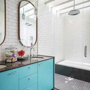 Example of a large danish master white tile and subway tile ceramic floor and gray floor bathroom design in New York with flat-panel cabinets, turquoise cabinets, white walls, an undermount sink, a hinged shower door, black countertops, a two-piece toilet and solid surface countertops