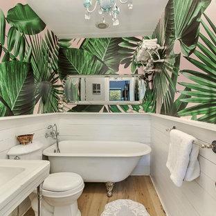 Mittelgroßes Kolonialstil Badezimmer En Suite mit freistehender Badewanne, Wandtoilette mit Spülkasten, weißen Fliesen, weißer Wandfarbe, hellem Holzboden, Sockelwaschbecken und beigem Boden in New York