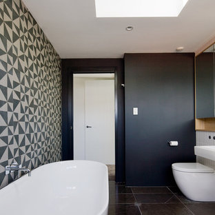 Inspiration for a contemporary bathroom in Sydney with a wall-mount sink, a freestanding tub, a one-piece toilet and black and white tile.