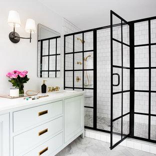 Idées déco pour une salle de bain classique avec des portes de placard blanches, un carrelage blanc, un carrelage métro, un mur blanc, un lavabo encastré, un placard avec porte à panneau encastré, une cabine de douche à porte battante et un banc de douche.