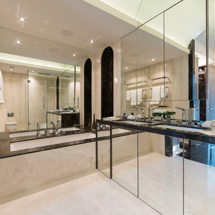 Large contemporary ensuite bathroom in London with a walk-in shower, a wall mounted toilet, beige tiles, beige walls, marble flooring, a built-in sink, marble worktops and a submerged bath.