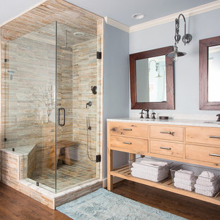 Diseño de cuarto de baño rural con armarios con paneles lisos, puertas de armario de madera oscura, ducha esquinera, baldosas y/o azulejos beige, paredes azules, suelo de madera oscura y bañera con patas