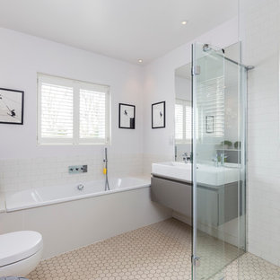 Photo of a contemporary ensuite bathroom in London with flat-panel cabinets, grey cabinets, a built-in bath, a wall mounted toilet, white tiles, metro tiles, white walls and a trough sink.