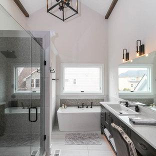 Стильный дизайн: большая главная ванная комната в стиле кантри с фасадами в стиле шейкер, искусственно-состаренными фасадами, отдельно стоящей ванной, открытым душем, унитазом-моноблоком, серой плиткой, керамической плиткой, белыми стенами, полом из керамической плитки, накладной раковиной, столешницей из искусственного кварца, белым полом, душем с раздвижными дверями и белой столешницей - последний тренд