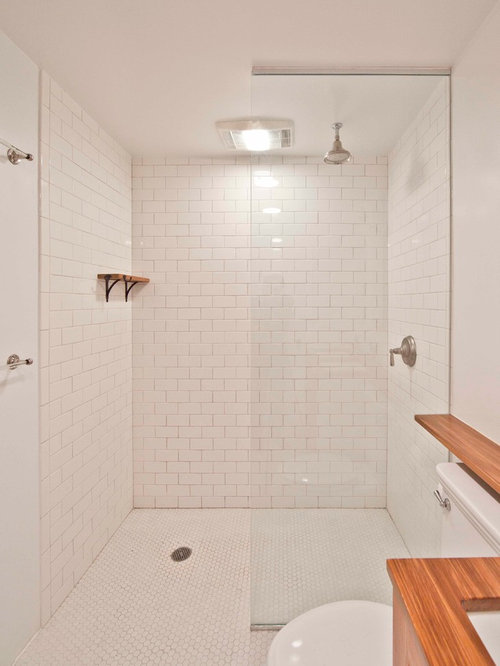 example of a trendy bathroom design in new york with subway tile and wood countertops