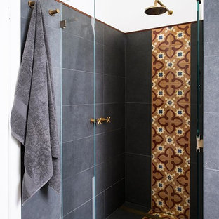 Small eclectic master multicolored tile and ceramic tile concrete floor doorless shower photo in Melbourne with an undermount sink, flat-panel cabinets, medium tone wood cabinets, solid surface countertops, a wall-mount toilet and white walls