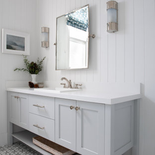 Corner shower - mid-sized transitional 3/4 mosaic tile floor, single-sink and shiplap wall corner shower idea in Perth with shaker cabinets, gray cabinets, a drop-in sink, a hinged shower door, white countertops, a built-in vanity and gray walls