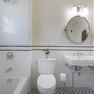 Modelo de cuarto de baño con ducha, de estilo americano, pequeño, con bañera empotrada, combinación de ducha y bañera, sanitario de dos piezas, baldosas y/o azulejos blancas y negros, baldosas y/o azulejos de cemento, paredes blancas, suelo de baldosas de cerámica, lavabo tipo consola y suelo multicolor