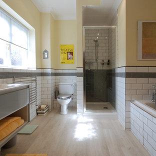 Réalisation d'une grand salle de bain design pour enfant avec un placard sans porte, une baignoire posée, une douche à l'italienne, un WC séparé, un carrelage jaune, des carreaux de céramique, un mur jaune, sol en stratifié, un plan vasque, un sol beige et une cabine de douche à porte battante.