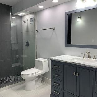 Foto di una stanza da bagno padronale moderna di medie dimensioni con consolle stile comò, ante blu, vasca ad alcova, doccia aperta, WC monopezzo, pareti grigie, pavimento in gres porcellanato, lavabo sottopiano, top in marmo, pavimento bianco, doccia aperta e top multicolore
