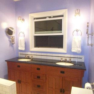 ロサンゼルスの中くらいのトランジショナルスタイルのおしゃれなマスターバスルーム (オーバーカウンターシンク、レイズドパネル扉のキャビネット、中間色木目調キャビネット、珪岩の洗面台、ドロップイン型浴槽、シャワー付き浴槽、一体型トイレ、グレーのタイル、セラミックタイル、紫の壁、セラミックタイルの床) の写真