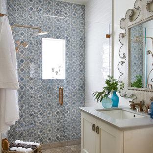 Mittelgroßes Shabby-Style Duschbad mit Schrankfronten im Shaker-Stil, gelben Schränken, Duschnische, blauen Fliesen, weißen Fliesen, Zementfliesen, weißer Wandfarbe, Keramikboden, Unterbauwaschbecken, Mineralwerkstoff-Waschtisch, beigem Boden und Falttür-Duschabtrennung in Los Angeles