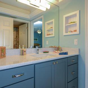 Modelo de cuarto de baño infantil, marinero, con lavabo bajoencimera, armarios con paneles empotrados, puertas de armario azules, encimera de granito, baldosas y/o azulejos grises y paredes azules