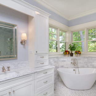 Elegant white tile and subway tile marble floor and white floor freestanding bathtub photo in Charlotte with recessed-panel cabinets, white cabinets, blue walls, an undermount sink and white countertops