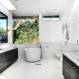 Ispirazione per una stanza da bagno padronale design di medie dimensioni con ante lisce, ante nere, vasca giapponese, doccia aperta, WC sospeso, piastrelle grigie, piastrelle in gres porcellanato, pareti bianche, pavimento in gres porcellanato, lavabo a bacinella e top in marmo