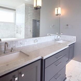 Immagine di una stanza da bagno padronale tradizionale di medie dimensioni con consolle stile comò, ante in legno scuro, vasca freestanding, piastrelle beige, piastrelle in pietra, pareti grigie, pavimento in marmo, lavabo sottopiano, top piastrellato e pavimento bianco