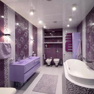 Ispirazione per una grande stanza da bagno padronale design con ante lisce, ante viola, vasca da incasso, WC sospeso, piastrelle di vetro, pareti viola, pavimento in gres porcellanato, lavabo integrato e pavimento grigio