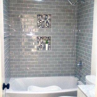 Exempel på ett mellanstort klassiskt en-suite badrum, med luckor med upphöjd panel, skåp i mörkt trä, en jacuzzi, en dusch i en alkov, en toalettstol med separat cisternkåpa, grå kakel, kakelplattor, grå väggar, kalkstensgolv, ett undermonterad handfat, marmorbänkskiva, grått golv och med dusch som är öppen