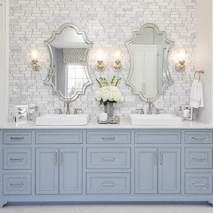 На фото: главная ванная комната в классическом стиле с фасадами с декоративным кантом, синими фасадами, белой плиткой, серой плиткой, белыми стенами, настольной раковиной и белым полом
