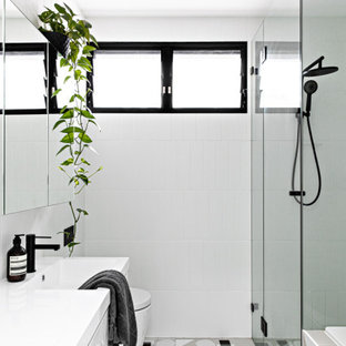 Inspiration for a small scandinavian master bathroom in Sydney with white cabinets, a drop-in tub, a one-piece toilet, white tile, ceramic tile, white walls, ceramic floors, a wall-mount sink, grey floor, a hinged shower door and white benchtops.