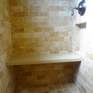 Aménagement d'une salle d'eau sud-ouest américain de taille moyenne avec un lavabo encastré, un placard avec porte à panneau surélevé, des portes de placard en bois brun, un plan de toilette en granite, une baignoire encastrée, une douche ouverte, un WC à poser, un carrelage marron, un carrelage de pierre, un mur beige et un sol en travertin.