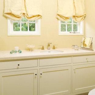Esempio di una piccola stanza da bagno con doccia chic con lavabo sottopiano, ante in stile shaker, ante beige, top in pietra calcarea, doccia ad angolo, WC monopezzo, pareti gialle, pavimento in cemento, piastrelle beige e piastrelle in ceramica