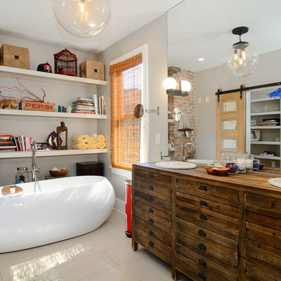 Eclectic beige tile freestanding bathtub photo in New York with a drop-in sink, furniture-like cabinets, dark wood cabinets, wood countertops, beige walls and brown countertops