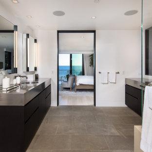 Foto på ett stort funkis en-suite badrum, med släta luckor, svarta skåp, ett fristående badkar, en hörndusch, ett nedsänkt handfat, bänkskiva i rostfritt stål och dusch med gångjärnsdörr