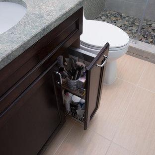 Cette image montre une petite douche en alcôve principale traditionnelle avec un lavabo encastré, un placard avec porte à panneau encastré, des portes de placard en bois sombre, un plan de toilette en granite, un WC à poser, un carrelage multicolore, des carreaux de porcelaine, un mur gris, un sol en carrelage de porcelaine, un sol beige, une cabine de douche à porte battante et un plan de toilette vert.