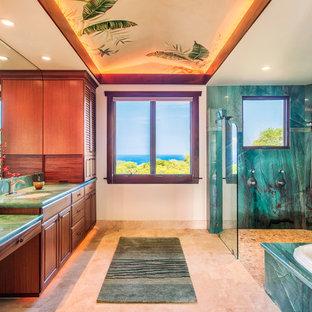 ハワイの広いトロピカルスタイルのおしゃれなマスターバスルーム (アンダーカウンター洗面器、レイズドパネル扉のキャビネット、濃色木目調キャビネット、御影石の洗面台、緑のタイル、白い壁、トラバーチンの床、ドロップイン型浴槽、石スラブタイル、バリアフリー、グリーンの洗面カウンター) の写真