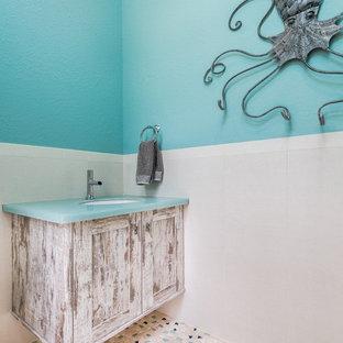 Ejemplo de cuarto de baño con ducha, costero, de tamaño medio, con armarios con paneles empotrados, puertas de armario con efecto envejecido, baldosas y/o azulejos azules y encimera de vidrio
