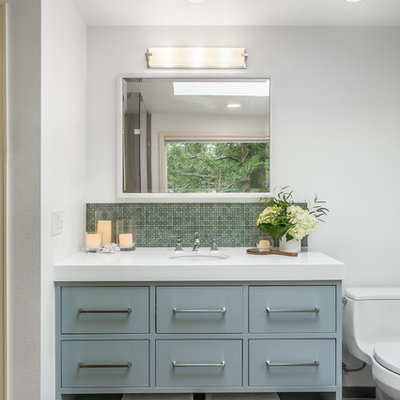 Inspiration for a transitional master porcelain tile bathroom remodel in Seattle with flat-panel cabinets, a one-piece toilet, white walls, an undermount sink, quartz countertops and blue cabinets